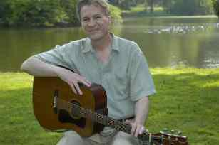 photo of Ben Tousley sitting by a lake and holding his guitar on his lap.