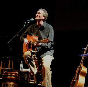 photo of Dennis Warner singing and playing guitar in concert
