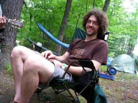 photo of Drew Grunseth sitting in a chair in a campsite in the woods