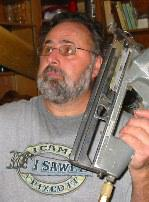 photo of Mark Morgan holding a nail gun for roofing