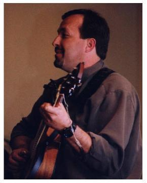 photo of Todd Werner in concert, singing and playing the guitar