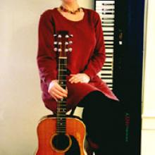 Photo of Carol with her guitar.