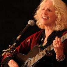 photo of Denise Jordan Finley singing & playing guitar in concert