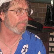 photo of Derek Lamson wearing a Hawaiian shirt and white baseball cap