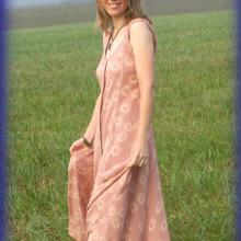 photo of Julie Rust wearing a long, sleeveless summer dress and standing in a field