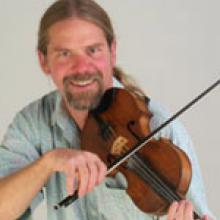photo of Kevin McMullin playing fiddle and smiling