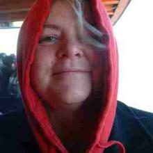 photo of Kiya Heartwood peering out from within a red hooded sweatshirt