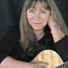photo of Priscilla Herdman holding her acoustic guitar