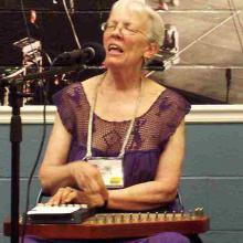 photo of Sally Campbell in concert, singing and strumming an autoharp.