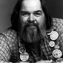 photo of Walter Craft wearing a checked flannel shirt, lots of buttons, and a big smile through his bushy beard
